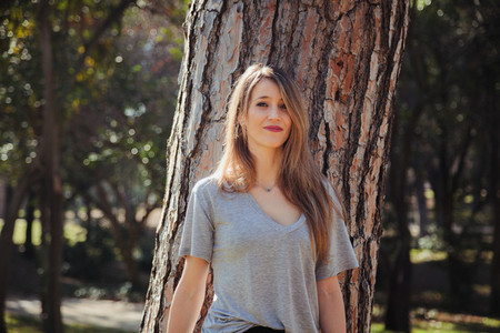 Young smiling blonde woman wearing a grey t shirt in the park