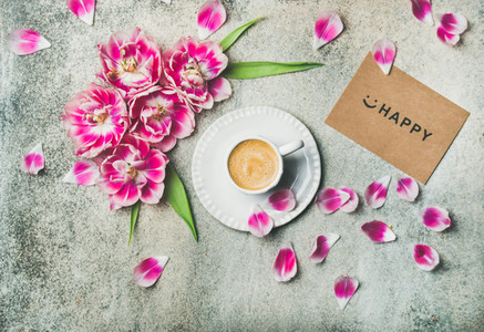 Cup of coffee surrounded with pink tulip flowers  marble background