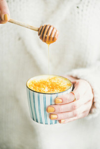 Turmeric latte  golden milk with honey in womans hands  close up