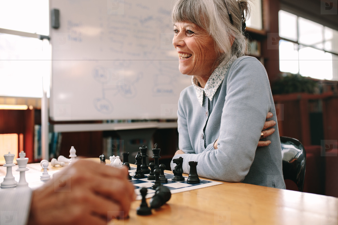 Senior woman playing chess in a classroom