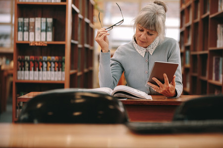 Woman reading a book in library