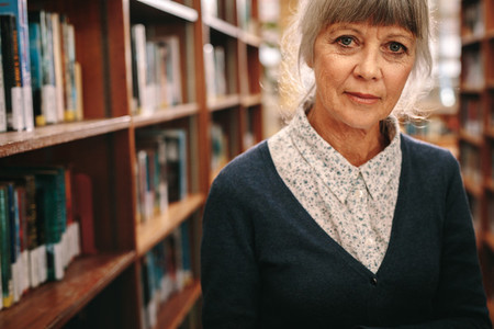 Portrait of a senior woman standing in a library
