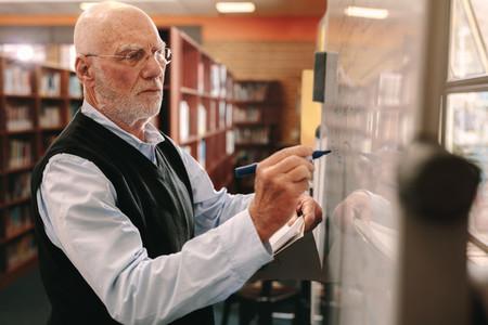 Senior man writing on the classroom board