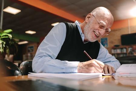 Senior man making notes in classroom