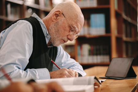 Senior man writing notes sitting in classroom