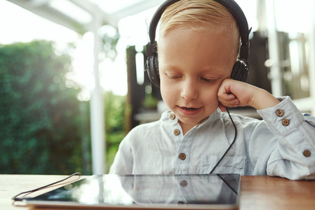 Adorable young boy listening to music