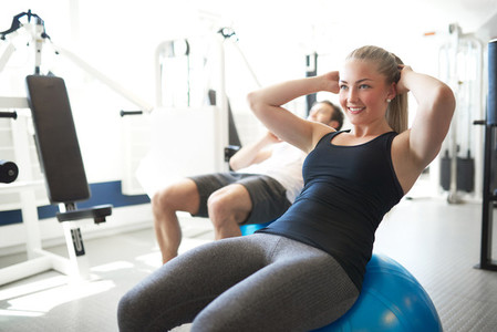 Fit Young Woman Doing Sit ups on Exercise Ball
