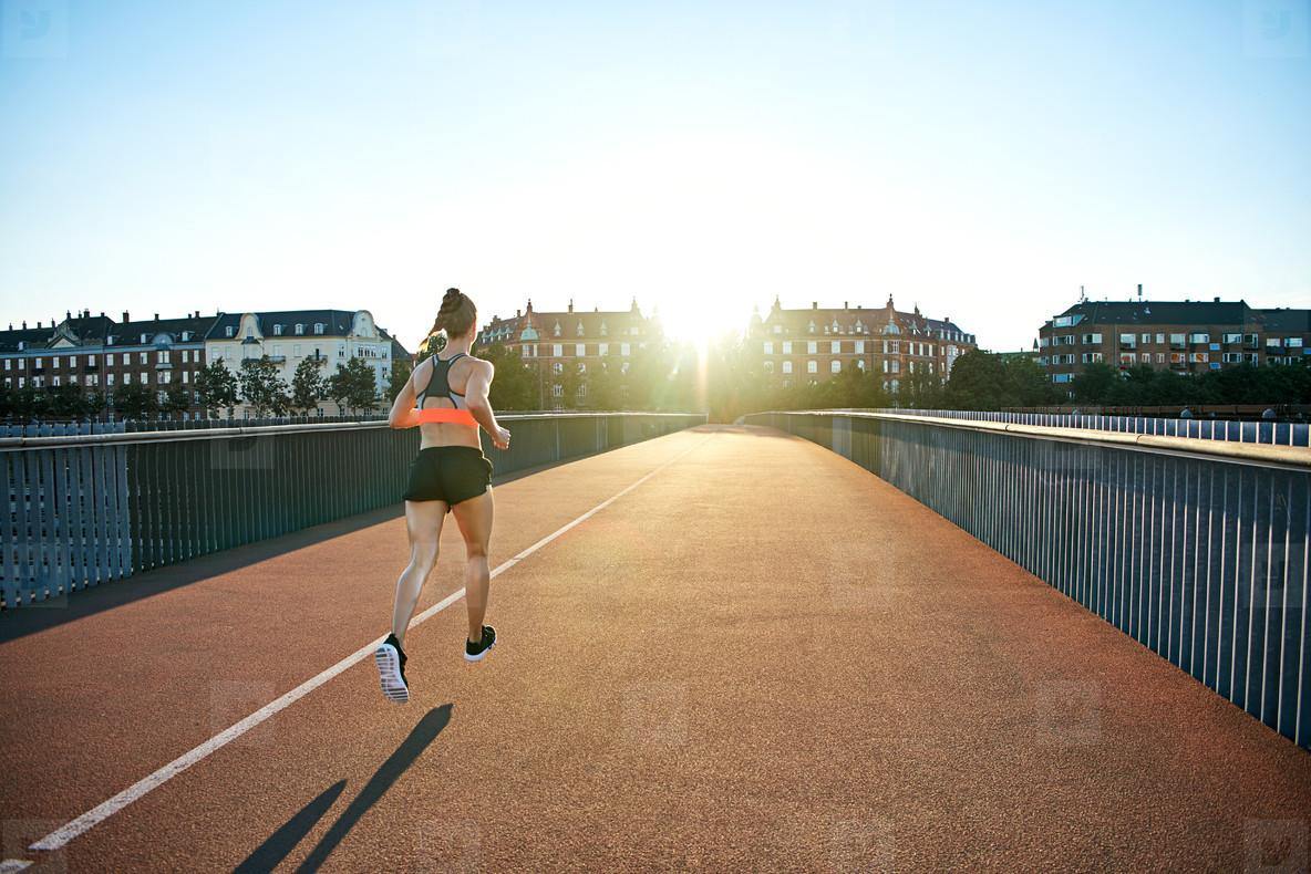 Rear view of athlete jogging toward bright sun
