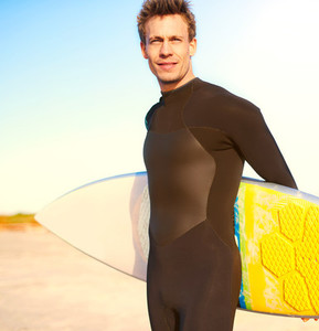 Handsome happy surfer holding a yellow surfboard