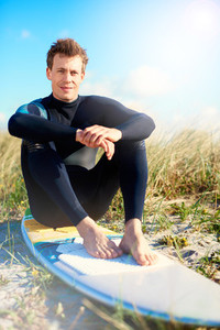 Handsome surfer relaxing sitting on his surfboard