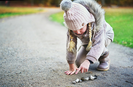 Little girl counts stones on a road