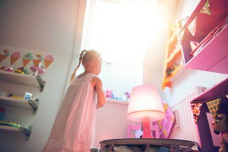 Little girl looking through window in bedroom