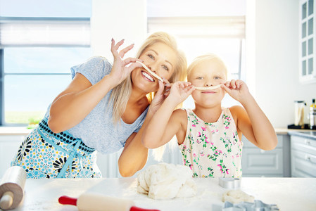 Playful Mum and daughter with pastry mustaches