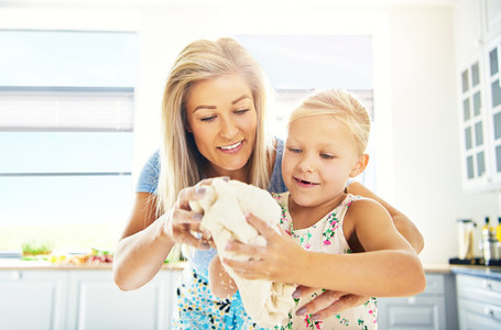 Cute little girl kneading dough with her mother