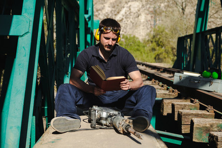 Young construction worker reading a book on old railway bridge