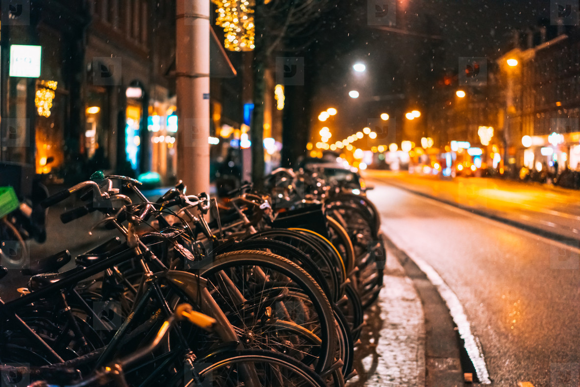 Bicycles parked along the road  night