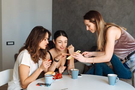 three woman friends breakfast in the kitchen