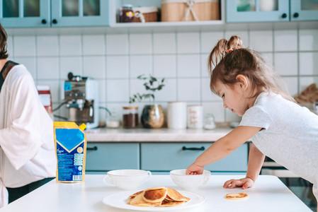 Little cute girl on kitchen is taking pancake