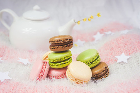 Delicious macarons with a tea in a teapot