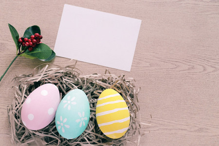 Pastel and colorful easter eggs in nest with blank card on woode