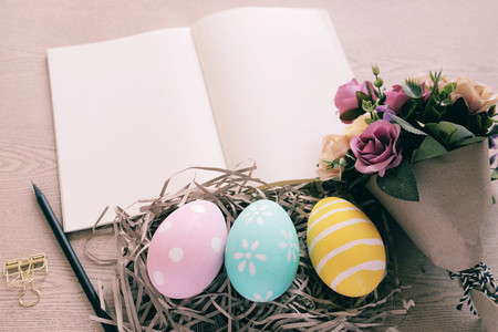 Pastel and colorful easter eggs in nest and bouquet of flower wi
