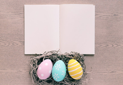 Pastel and colorful easter eggs on nest with blank notebook on w