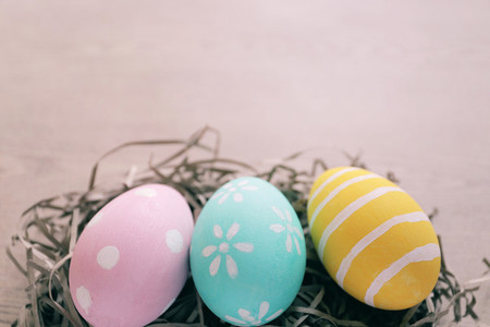 Pastel and colorful easter eggs on nest with wooden background a