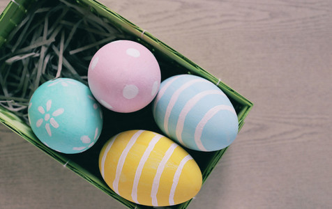 Pastel and colorful easter eggs in nest and basket on wooden bac