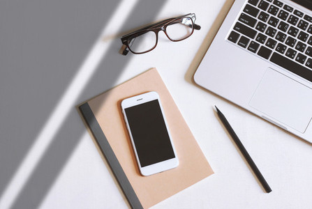 Flat lay photo of office desk with laptop  smartphone  eyeglasse