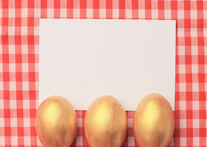 Golden easter eggs on red checkered tablecloth background with b