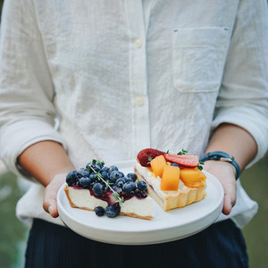 Close up woman hands holding plate of blueberry pie and mango wi