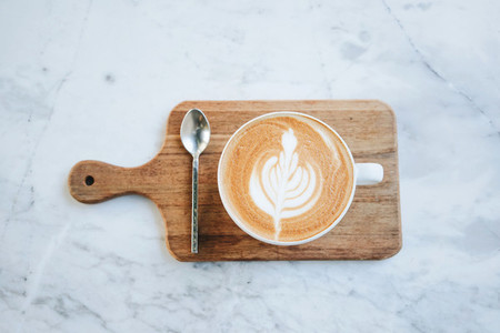 Top view of hot latte coffee on wooden tray on marble table back