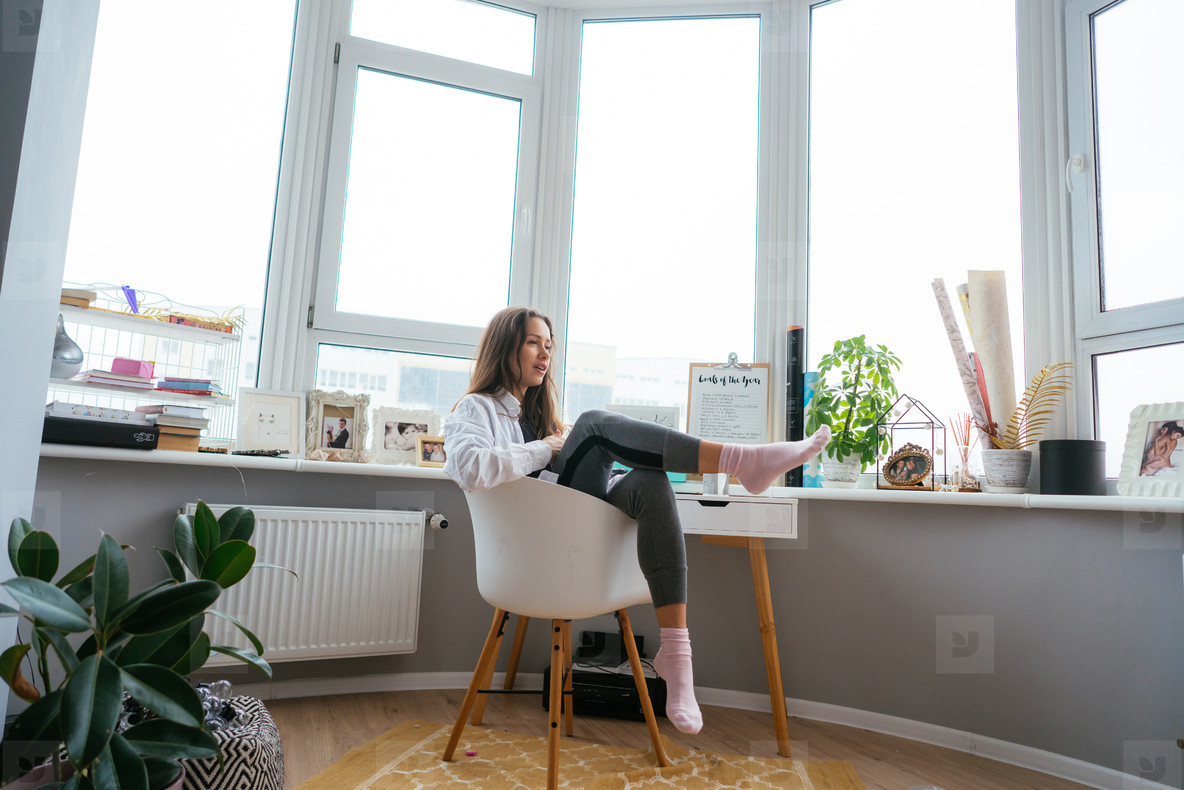 Young woman on chair near the window