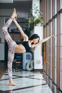 Young attractive woman practicing yoga near window