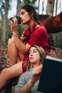 Young women reading a book and taking photos in the forest