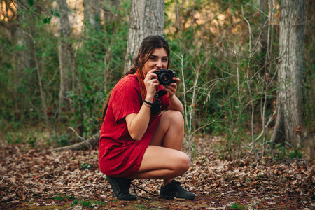 Young smiling woman taking photos in the forest wearing a dress