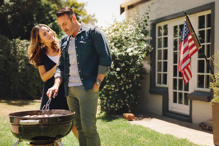 Happy couple making a barbeque in their backyard