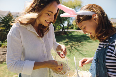 Happy mother and daughter putting sweets in baskets