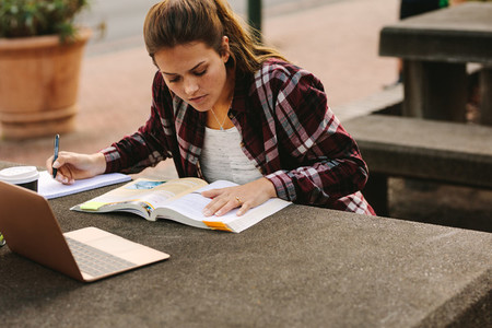 Female student making notes at college campus