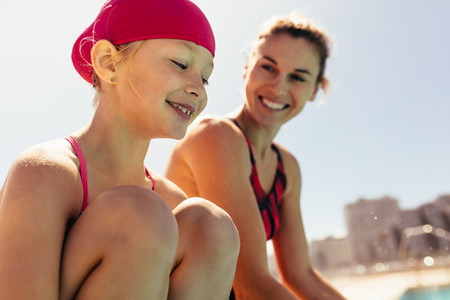 Smiling child with swimming coach