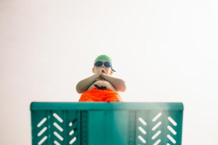Boy on diving platform at pool