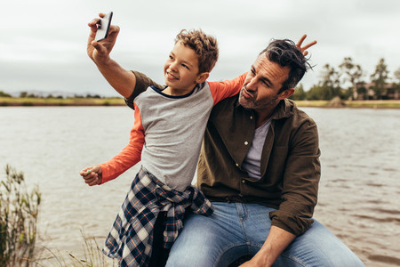 Father and son having fun taking selfie outdoors