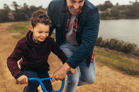 Father helping his son learn to ride a bicycle