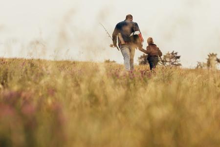 Man walking with kid holding fishing rods