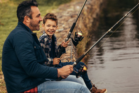 Happy man and kid fishing in a lake
