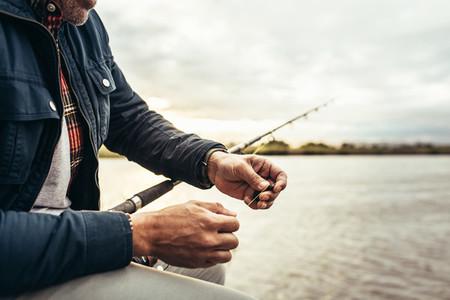 Close up of a man sitting near a lake to do fishing