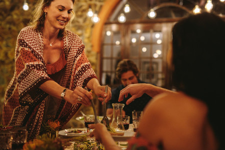 Woman serving food to friends at dinner party