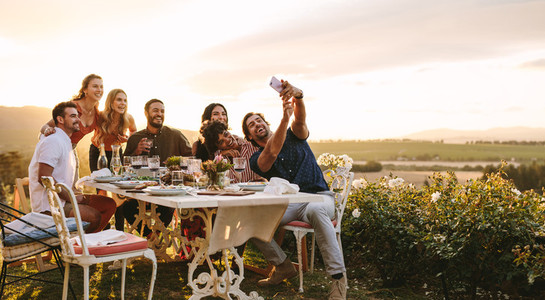 Group of friends taking selfie at dinner party
