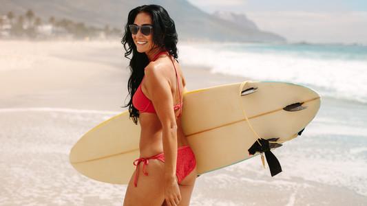 Beautiful female surfer on beach