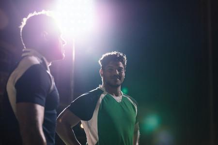 Sportsmen standing on rugby field under lights